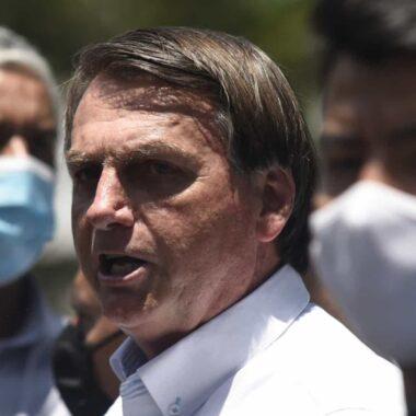 Sem máscara, Bolsonaro abraça banhistas e pega crianças no colo em praia